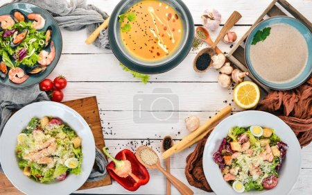 Photo for A set of healthy food in plates. Caesar salad, seafood, pumpkin soup and mushrooms. Top view. On a wooden background. Copy space. - Royalty Free Image