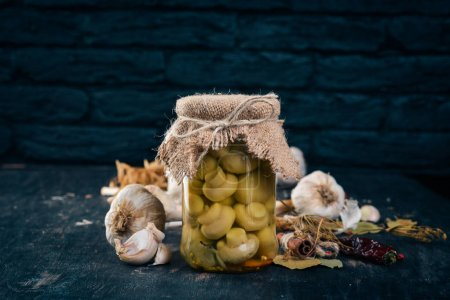 Photo for Marinated mushrooms in a jar. Stocks of food. Top view. On a wooden background. Copy space. - Royalty Free Image