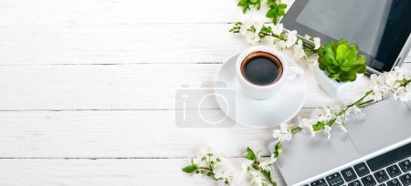 Photo for Laptop with coffee and flowers. Business. On a wooden background. Top view. Copy space. - Royalty Free Image