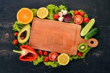 Photo pour Alimentation saine. Légumes et fruits sur fond noir en bois. Vue de dessus. Espace copie. - image libre de droit