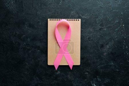 Photo pour Journée mondiale du cancer : Ruban de sensibilisation au cancer du sein. Vue de dessus. Espace de copie gratuit . - image libre de droit