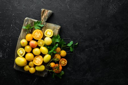 Photo for Yellow tomatoes on black stone background. Top view. Free space for your text. - Royalty Free Image