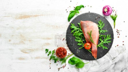 Photo for Raw sea red perch with rosemary and spices on a black plate. Seafood. Top view. Free space for your text. - Royalty Free Image