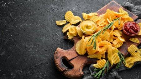 Photo pour Croustilles avec ketchup et sauce moutarde. Collations à la bière sur fond de pierre noire. Vue en haut. - image libre de droit