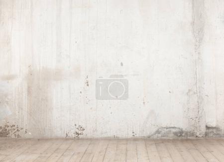 Photo pour Texture d'un vieux mur de béton avec des fissures et un plancher de bois - image libre de droit