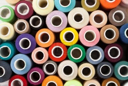 Background of colorful sewing threads on white table