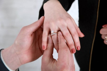 Photo for Grooms hand putting a wedding ring on the brides finger - Royalty Free Image