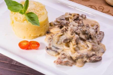 Veal stewed with onions and mushrooms in gentle creamy sauce, is served with mashed potatoes with cheese