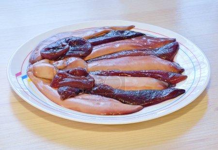 Photo pour Œufs crus et laitance dans le sac de hareng se trouvent horizontalement dans un plat blanc en céramique sur une table en bois - image libre de droit