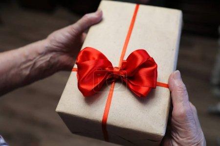 Photo pour Boîte de cadeau avec arc rouge dans la macro de mains de grand-mère - image libre de droit