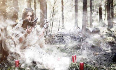 Photo pour Magicien de fées. Un sorcier avec une sphère de verre, un sort magique et un rituel. Ancien avec un bâton et une croix dans la forêt. Magie noire et blanche. Un sort dans un vieux livre . - image libre de droit