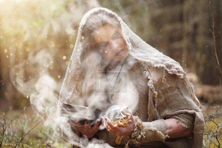 Photo pour Un homme en soutane passe un rituel dans une forêt sombre avec une boule de cristal et un livre - image libre de droit