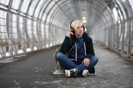 Photo pour Jeune fille écoute de la musique dans les grands écouteurs dans le tunnel du métro - image libre de droit