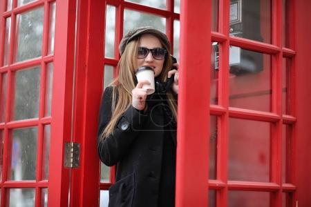 Photo pour Belle jeune fille dans une cabine téléphonique. La fille parle au téléphone depuis la cabine. Cabine téléphonique anglaise dans la rue et une femme parlant au téléphone. - image libre de droit