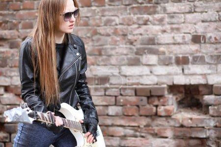 Una chica músico de rock en una chaqueta de cuero con una guitarra