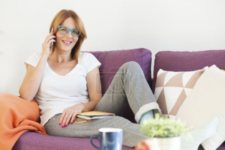 woman in the living room talking a phone