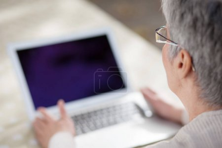 Older woman in a park using laptop computer