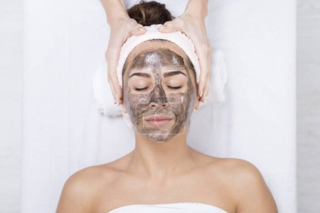 woman in a spa with black facial mask