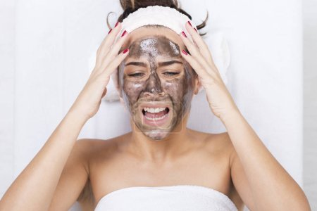 Unhappy woman in a spa with black facial mask