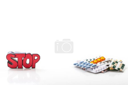 Colorful drugs and pills with sign STOP