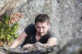 Muž po skalní stěně