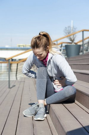 Woman having a stomachache during jogging