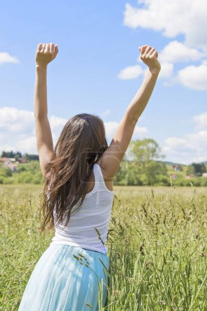 Happy and enjoying young woman on a meadow