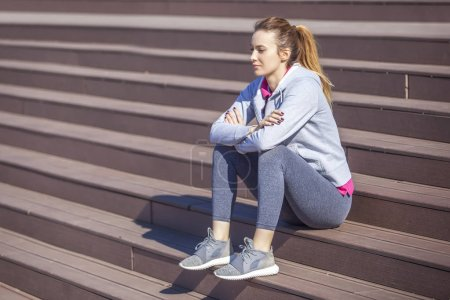 Woman with abdominal pain sitting on the steps