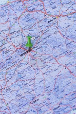 Green push pin pointing at Madrid