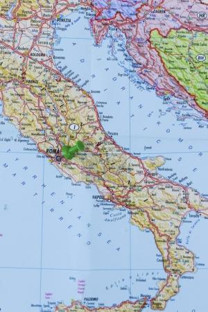 Green push pin pointing at Rome