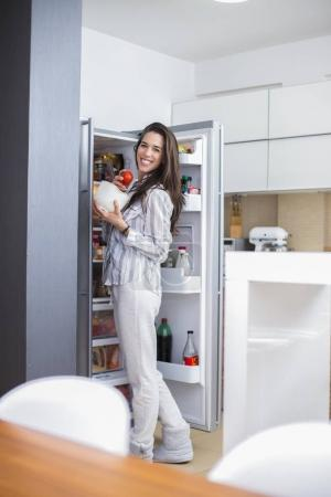 woman in the kitchen in front of the refrigerator takes food