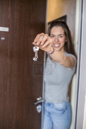 woman shows keys from her apartment