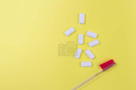 Toothbrush with chewing gum isolated on yellow background