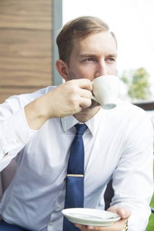 Modern businessman sitting at coffee shop