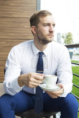 Modern businessman sitting at coffee shop