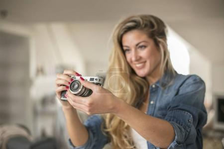 Indoor smiling lifestyle portrait of pretty young woman with cam