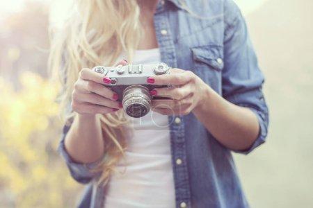 pretty woman with retro camera on terase