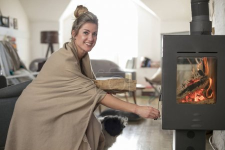 Beautiful middle-aged woman inserts wooden logs into the fireplace. Living room with fire.