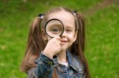 Little girl explores at nature through a magnifying glass