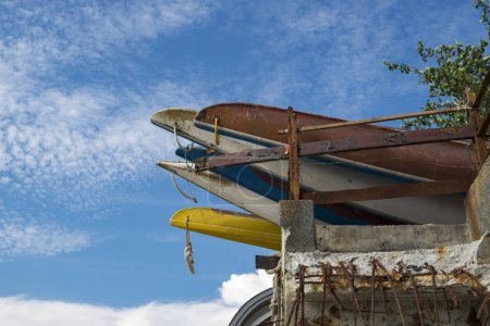 stacking inline blue and yellow kayaks over cloudy sky background