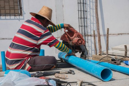 Worker cutting pvc pipe at construction site