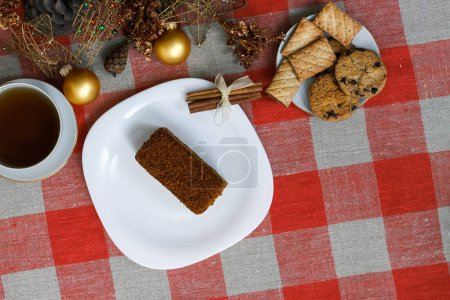 Cake on a white plate on a checkered tablecloth with tea, biscuits, cinnamon on a background of a New Year's Christmas tree. New concept. For holiday. View from above.