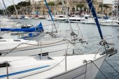 Yachts moored at Msida Marina in Malta. Sail boats in a row on docks at seaside harbor.