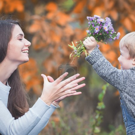 Child gives to happy mother flowers. Fall colors background