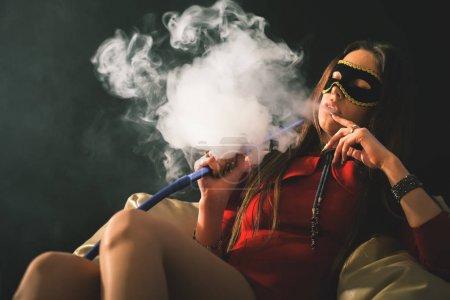Young, beautiful girl with carnival mask smoke a hookah