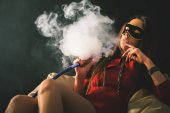 Young, beautiful girl with carnival mask smoke a hookah