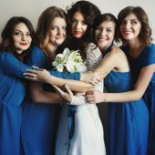 Bride in the hugs of her bridesmaid in blue
