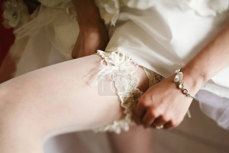 Bride adjusts a lace garter on a stocking...
