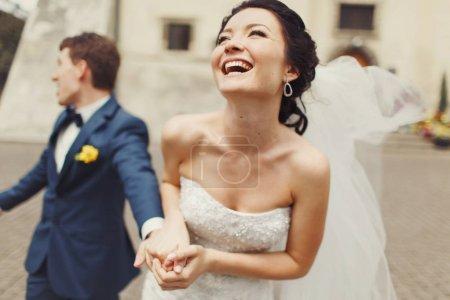 Bride laugh sparkling holding groom's hand