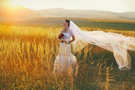 Photo pour Mariée aime le vent et le soleil debout sur le terrain - image libre de droit